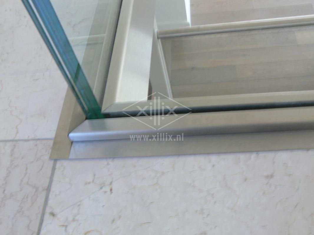 rvs randafwerking op de vloer bij een volledig glazen balustrade xillix.nl